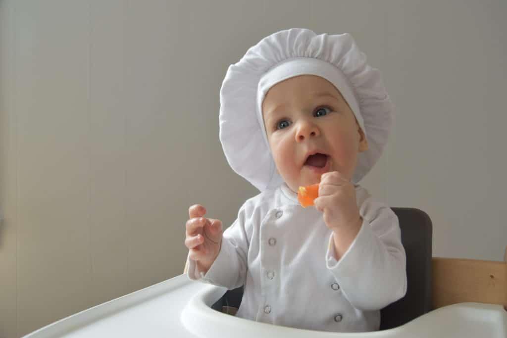 bébé qui mange un morceau de fruit avec une toque de cuistot